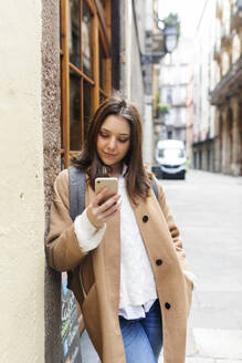 Young woman checking her phone in the city, Barcelona, Spain - VABF02538