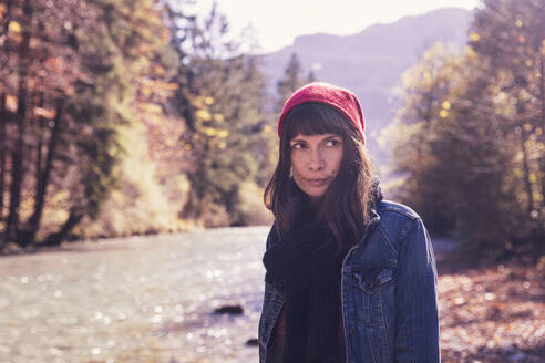 Woman wearing red woolly hat and denim jacket at riverside - DHEF00014
