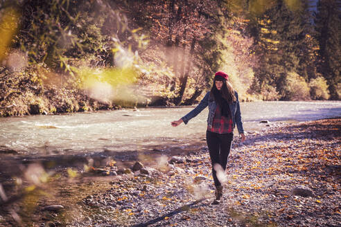 Woman wearing red woolly hat and denim jacket walking at riverside in autumn - DHEF00020