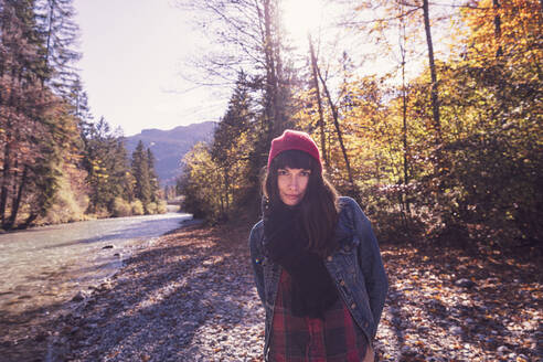 Woman wearing red woolly hat and denim jacket at riverside in autumn - DHEF00026