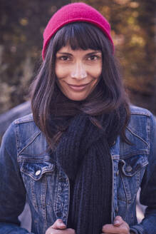 Portrait of smiling woman wearing red woolly hat and denim jacket - DHEF00029