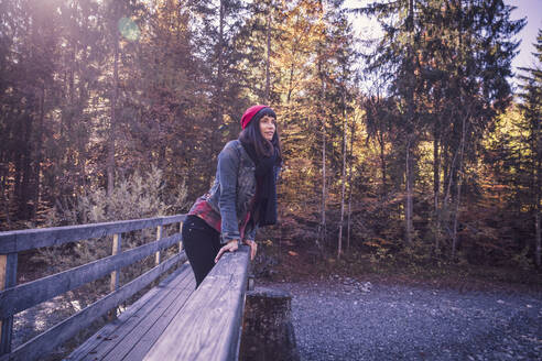 Woman wearing red woolly hat and denim jacket on a bridge in autumn - DHEF00032