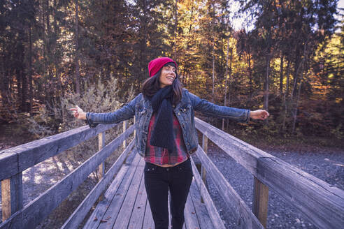 Woman wearing red woolly hat and denim jacket on a bridge in autumn - DHEF00035