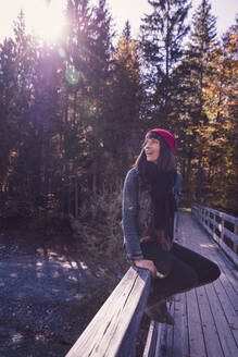 Woman wearing red woolly hat and denim jacket sitting on a railing and looking sideways - DHEF00038