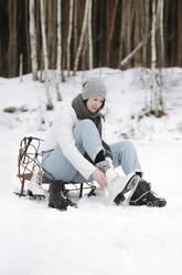 Woman putting on ice skates on snow field - EYAF00812
