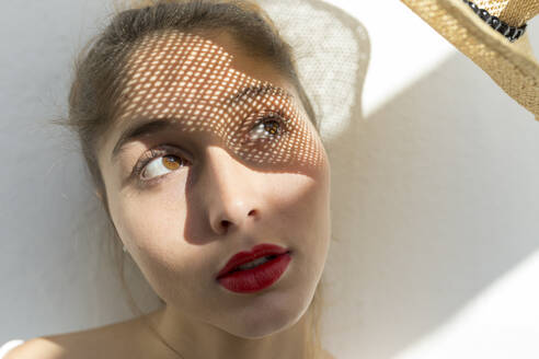 Portrait of young woman with shadow on her face - JPTF00443