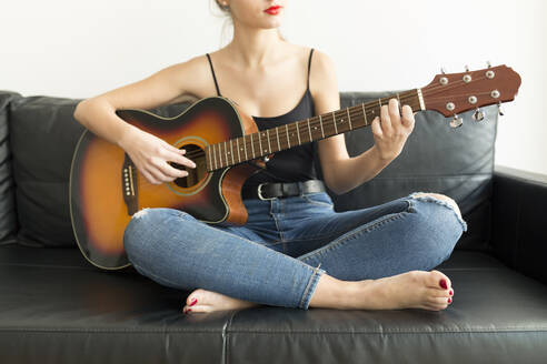 Crop view of young woman sitting on couch playing guitar - JPTF00449