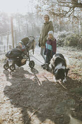 Mother with daughters and border collie during forest walk in autumn - DWF00533