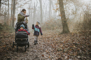 Mother with daughters during forest walk in autumn - DWF00545