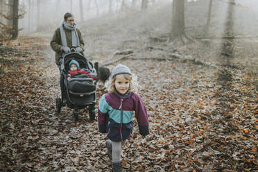 Mother with daughters and border collie during forest walk in autumn - DWF00548