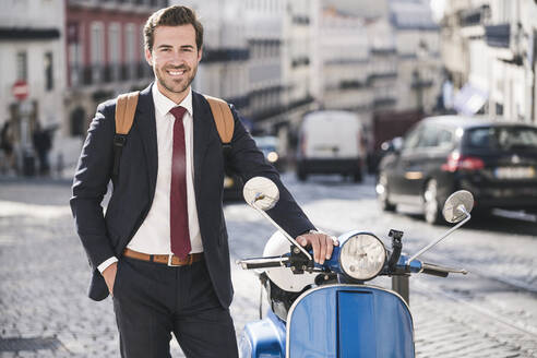 Portrait of smiling young businessman with motor scooter in the city, Lisbon, Portugal - UUF20081