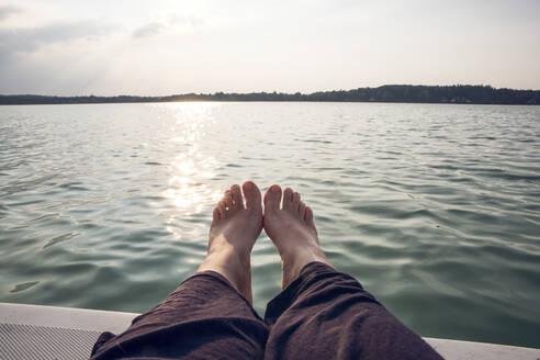 Man barefoot on sailing boat at sunset - MAMF01042
