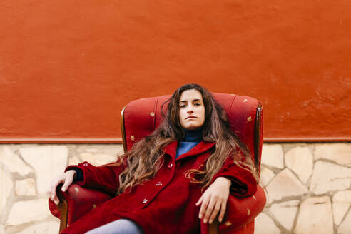 Portrait of confident young woman sitting on lounge chair - TCEF00042