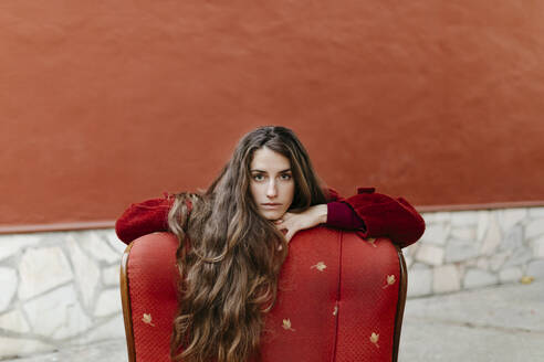 Portrait of selfconfident young woman with long brown hair leaning on back rest of red lounge chair - TCEF00048