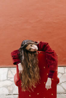 Portrait of young woman with long brown hair leaning on backrest of red lounge chair - TCEF00054