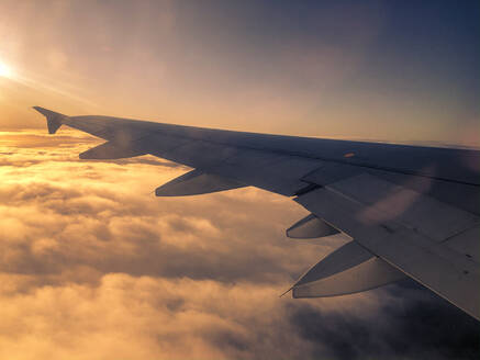 Aircraft wing during flight above clouds at sunset - TEBF00020