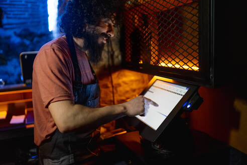 Young man, working in bar, using coputer cashier - CJMF00235