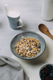 Bowl of granola with jug of yogurt in background - JMHMF00035