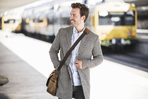 Smiling young businessman at the train station looking around - UUF20140
