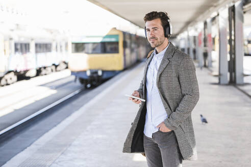 Young businessman with cell phone and headphones at the train station - UUF20149