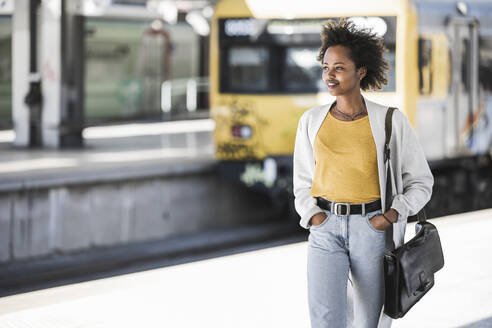 Smiling young woman at the train station - UUF20155