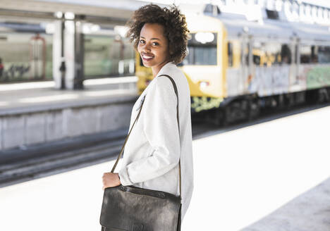 Portrait of smiling young woman at the train station - UUF20158