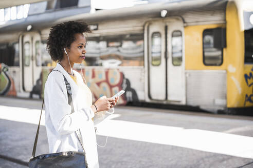 Young woman with cell phone and earphones at the train station - UUF20161