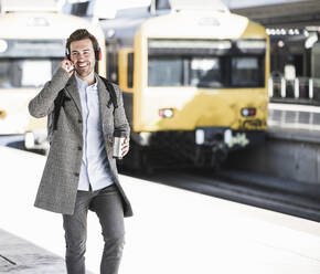 Happy young businessman with coffee mug and headphones walking at the train station - UUF20170