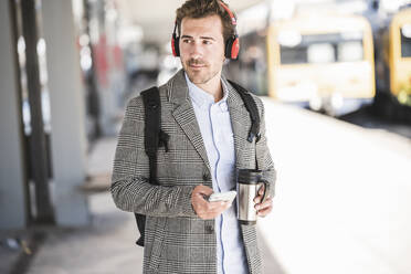 Young businessman with cell phone and headphones at the train station - UUF20173