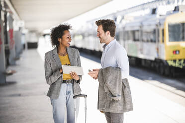 Young businessman and happy businesswoman using tablet together at the train station - UUF20182