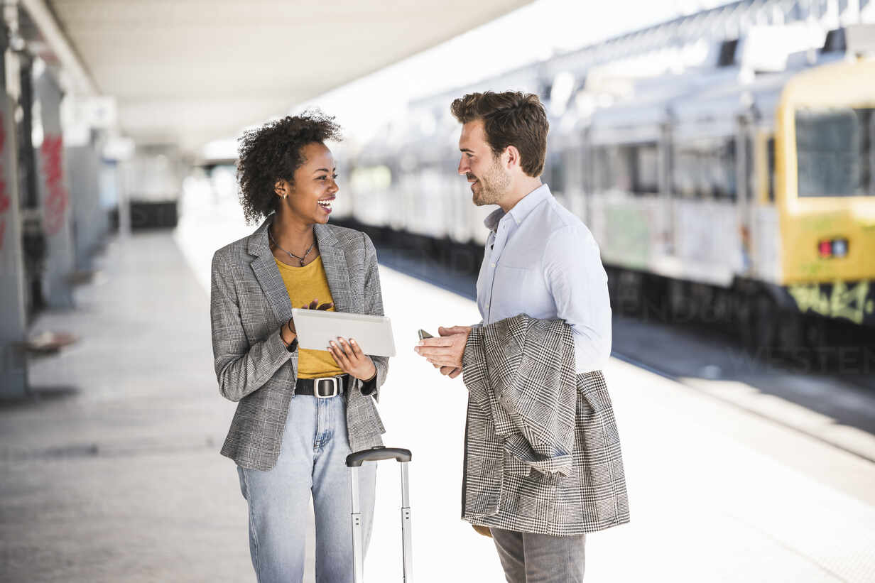 Young businessman and happy businesswoman using tablet together at the train station - UUF20182 - Uwe Umstätter/Westend61