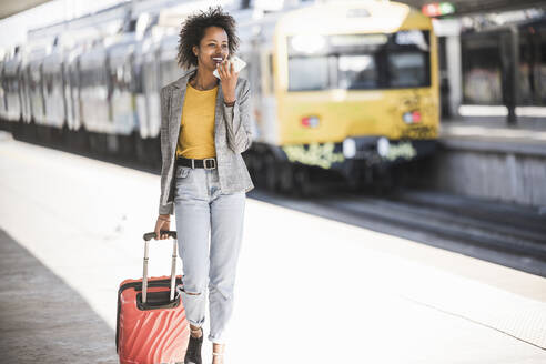 Smiling young woman using cell phone at the train station - UUF20191