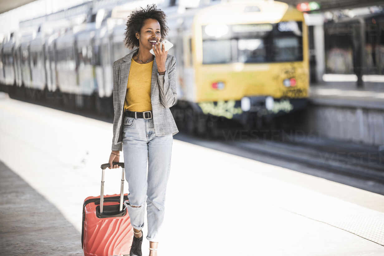 Smiling young woman using cell phone at the train station - UUF20191 - Uwe Umstätter/Westend61
