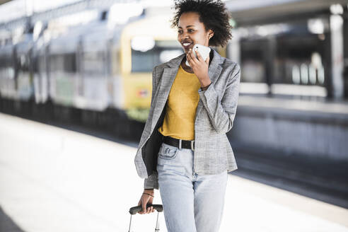 Smiling young woman using cell phone at the train station - UUF20194