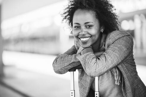 Portrait of smiling young businesswoman with suitcase at the train station - UUF20200