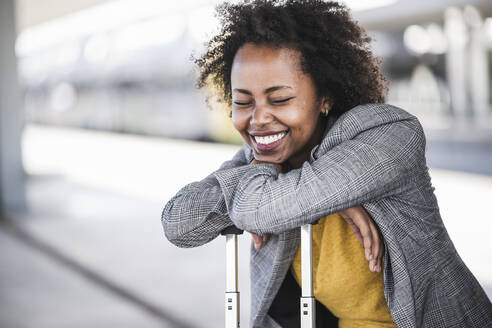 Happy young businesswoman with suitcase at the train station - UUF20203