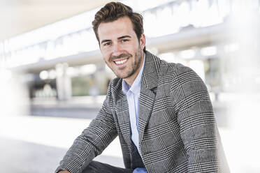 Portrait of smiling young businessman at the train station - UUF20209