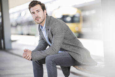Portrait of young businessman sitting at the train station - UUF20212