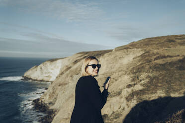Rear view of young blond woman with smartphone at the coast - MTBF00308