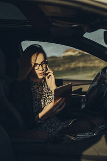 Young blond woman using smartphone and tablet in the car - MTBF00311