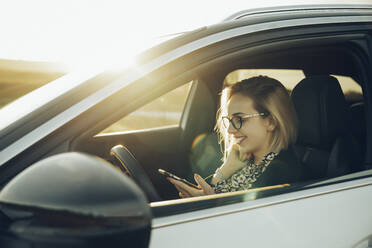 Young blond woman using smartphone in the car - MTBF00314