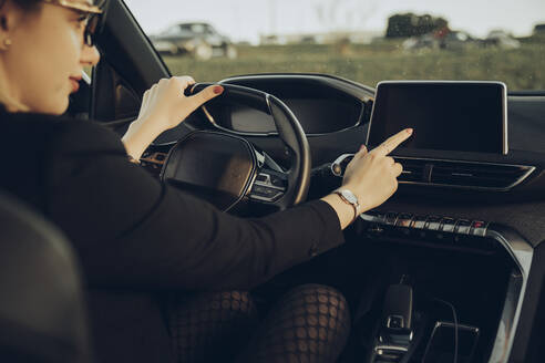 Young woman using navigation device in car - MTBF00317