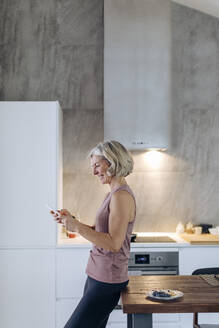 Mature woman using cell phone in kitchen at home - SODF00534