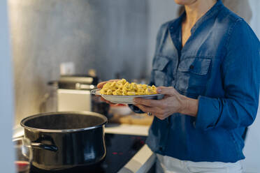 Close-up of woman holding a plate with tortellini in kitchen at home - SODF00603