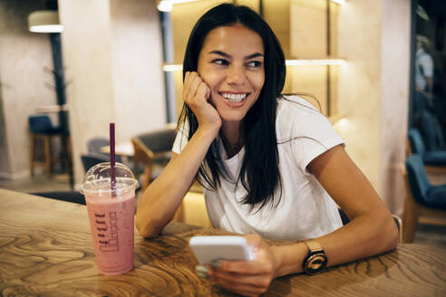Black-haired woman drinking a smoothie and using smartphone in cafe - OYF00104