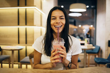 Black-haired woman drinking a smoothie in cafe - OYF00107