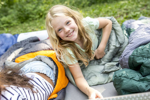 Little girl lying on sleeping bag, looking at camera - WESTF24488