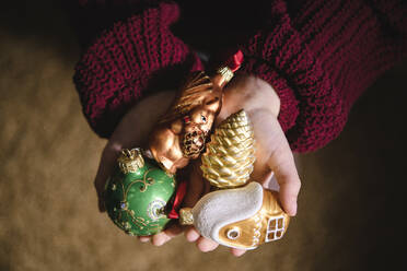 Various Christmas ornaments in girl's hand - EYAF00823