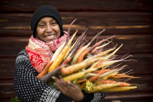Woman holding freshly picked carrots - JOHF05540