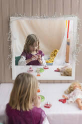 Mirror image of little girl playing at home - PSIF00367